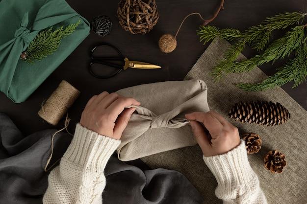 Mains de femme emballant des cadeaux furoshiki cadeaux de noël vert alternative écologique