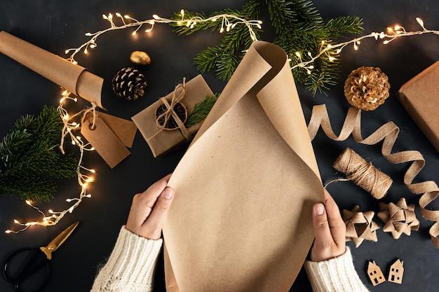 Mains de femme emballant des cadeaux de noël verts alternatifs écologiques avec du papier kraft recyclé