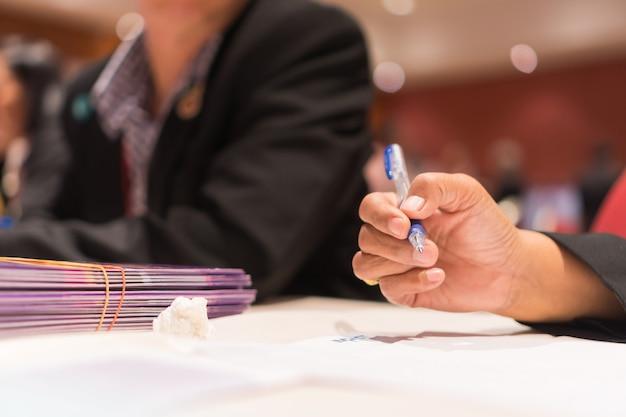 Mains de femme enseignant tenant un stylo pour vérifier la signature