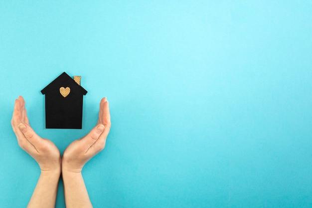 Les mains de la femme entourent une maquette d'une maison sombre sur fond bleu