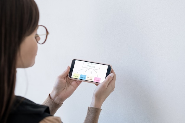 Mains de femme entraîneur d'affaires tenant smartphone avec organigramme de prise de décision en se tenant debout par tableau blanc