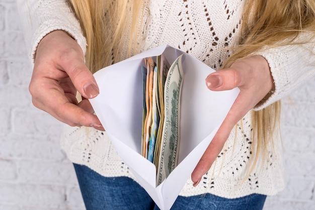 Mains de femme avec enveloppe pleine de billets en dollars et en euros