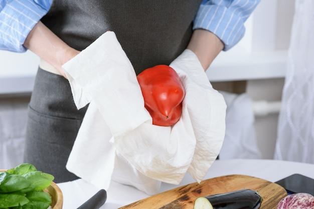 Mains de femme essuyez le poivron rouge avec une serviette de cuisine blanche cuisson à la maison concept