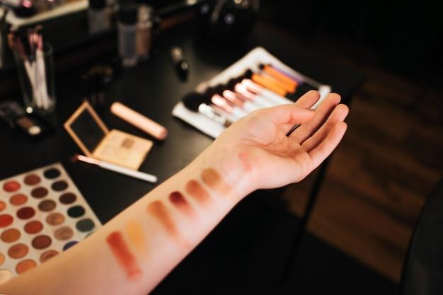 Mains de femme avec des exemples de fards à paupières sur la peau.