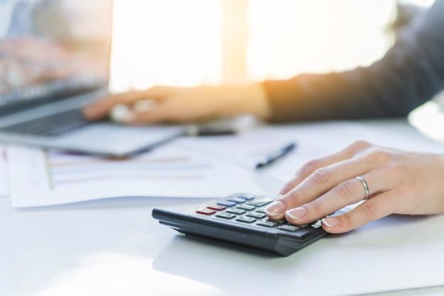 Mains de femme faisant des calculs sur le lieu de travail