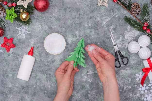 Mains de femme faisant une décoration artisanale de noël