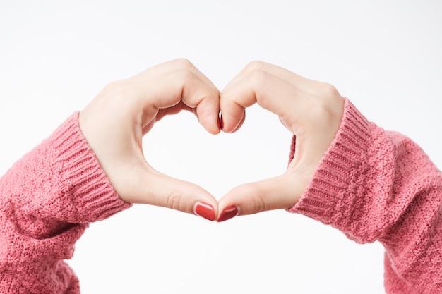 Mains de femme faisant une forme de coeur sur un fond blanc isolé