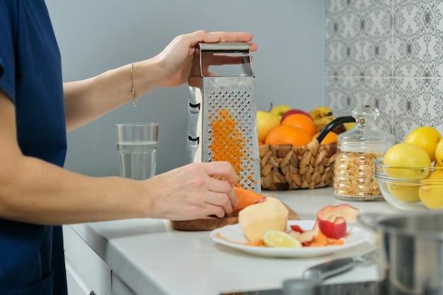 Mains de femme frotter la carotte et la pomme sur une râpe en métal dans la cuisine