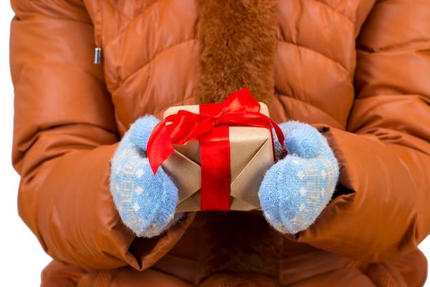 Les mains de la femme avec des gants d'hiver tenant une boîte-cadeau rouge de noël.