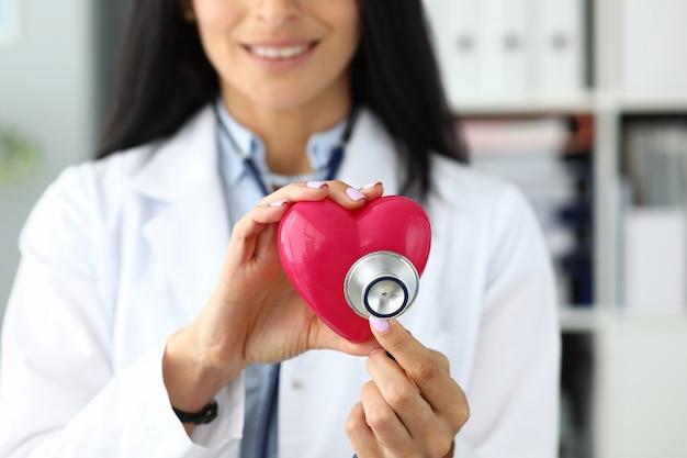 Mains de femme gp tenant la tête de stéthoscope près de coeur jouet rouge