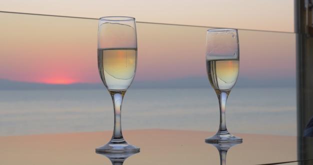 Les mains de la femme et de l'homme tintent des verres de champagne sur fond de mer coucher de soleil vue rapprochée
