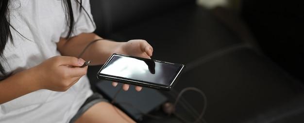 Les mains de la femme image recadrée chargent un smartphone alors qu'il était assis sur le canapé en cuir noir