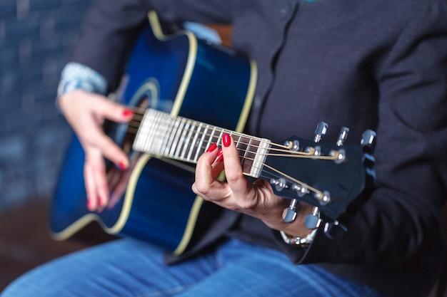 Mains de femme jouant de la guitare acoustique, close up