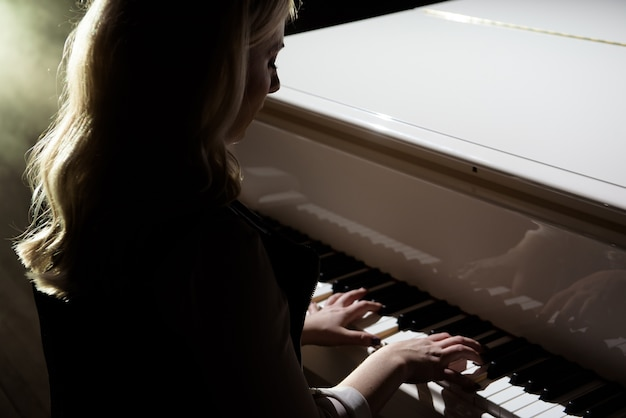 Mains de femme jouant un piano, instrument de musique.
