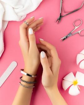 Mains de femme avec manucure française blanche à la mode