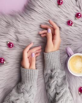 Les mains de la femme avec la manucure à la lavande à la mode, la conception des ongles de noël d'hiver