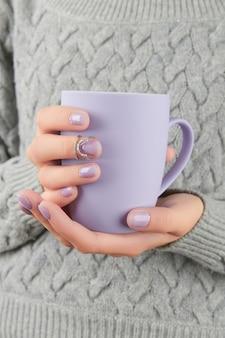 Mains de femme avec manucure à la lavande à la mode tenant une coupe d'ongles de noël d'hiver