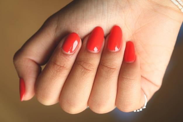 Mains de femme avec manucure moderne rouge, main féminine avec belle manucure élégante française orange naturelle