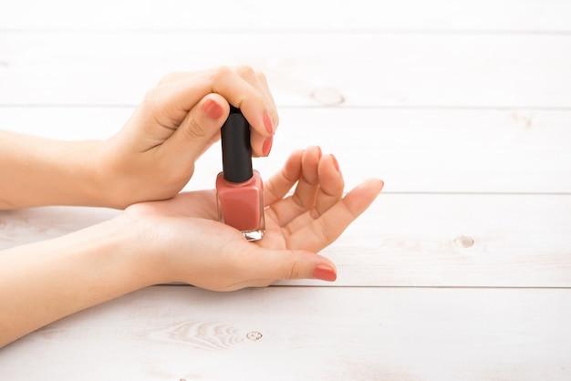 Mains d'une femme avec une manucure nue et une bouteille de vernis à ongles