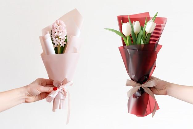 Mains de femme avec manucure tenant des fleurs de printemps.