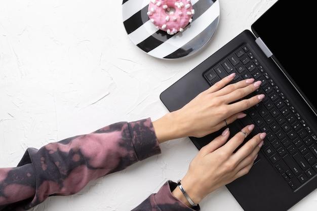 Les mains de la femme manucurée dans un sweat à capuche rose tendance tapant sur un ordinateur portable.