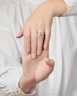 Mains de femme manucurées avec des bijoux minimalistes à la mode