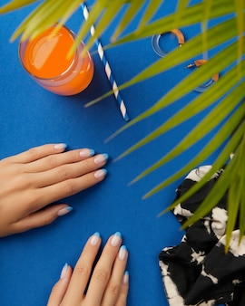 Mains de femme manucurées avec des vêtements et accessoires d'été