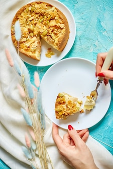 Mains de femme méconnaissable manger un morceau de tarte aux pommes ou aux poires avec des noix au caramel sur table bleue avec la lumière du soleil