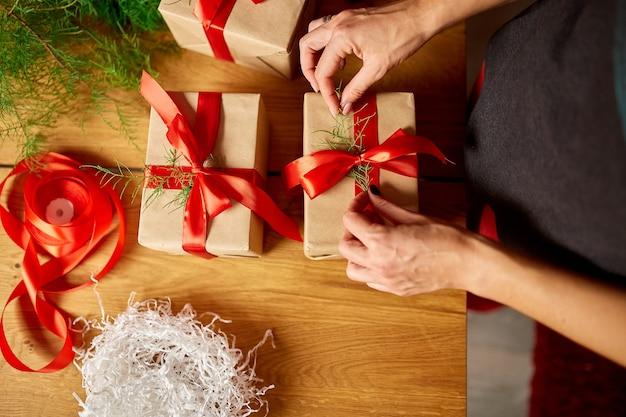 Mains de femme méconnaissable recadrée emballant le cadeau de noël