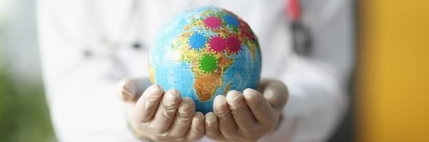 Les mains de la femme médecin dans les gants tiennent le globe.