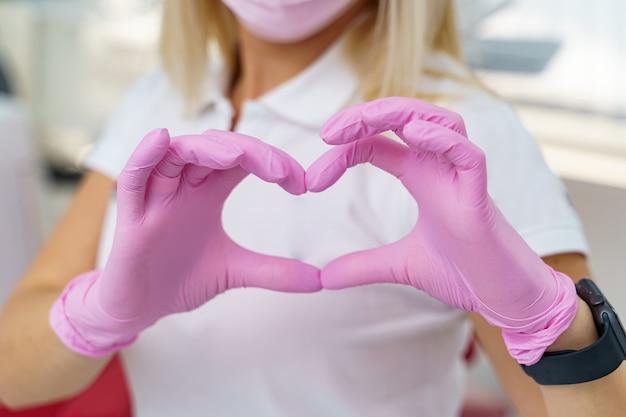 Les mains de la femme médecin montrant la forme du coeur. gros plan des mains du médecin. aide médicale, prophylaxie ou concept d'assurance. soins de cardiologie, santé, protection et prévention. concept de coeur sain