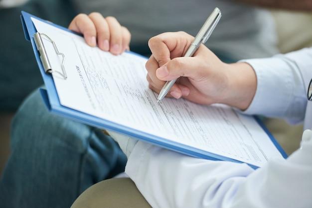 Mains de femme médecin non reconnaissable remplissant le formulaire dans le presse-papiers