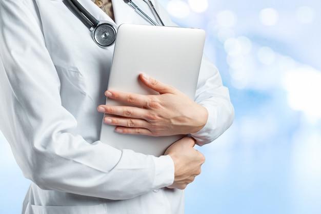 Mains de femme médecin avec ordinateur portable