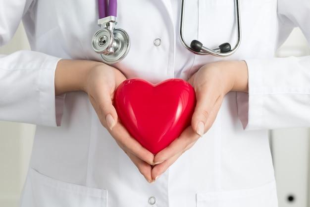 Mains de femme médecin tenant un coeur rouge. gros plan des mains du médecin. aide médicale, prophylaxie ou concept d'assurance.