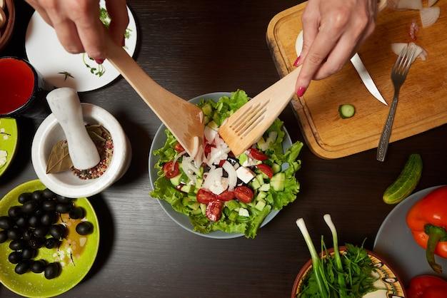 Mains de femme mélangeant une salade grecque saine