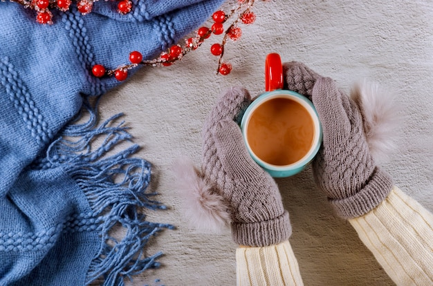 Mains de femme en mitaines de laine tricotées tenant une tasse de cacao chaud