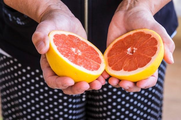 Les mains de femme mûre prennent un pamplemousse. couleurs et offre un concept pour une vie et un mode de vie sains. fruits frais de saison coupés au milieu. demi mesure