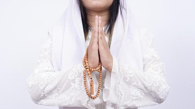 Mains de femme musulmane asiatique portant des perles de prière accueillant des invités