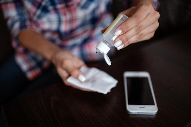 Mains de femme nettoyant un téléphone