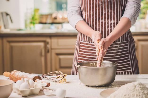 Mains de femme pétrir la pâte dans un bol en fer. une femme en tablier rayé cuisine dans la cuisine