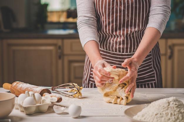 Mains de femme pétrir la pâte sur la table de la cuisine. une femme en tablier rayé cuisine dans la cuisine