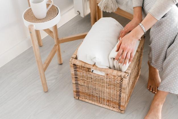 Mains d'une femme plier un plaid dans un panier en bois