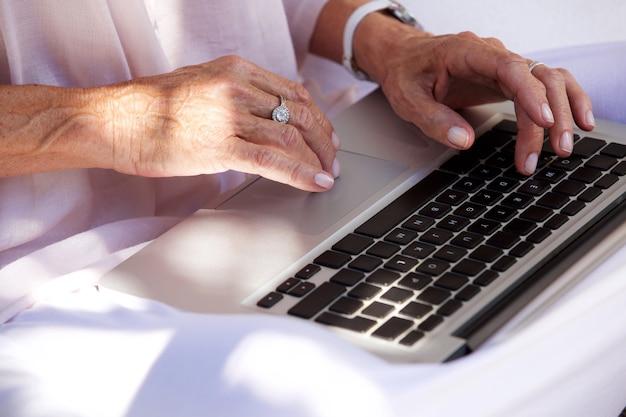Des mains de femme plus âgée tapant sur un ordinateur portable