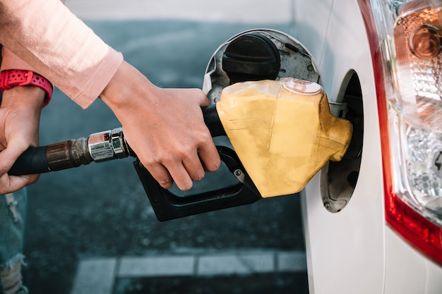 Mains de femme pompant du carburant à essence dans la voiture à la station d'essence.