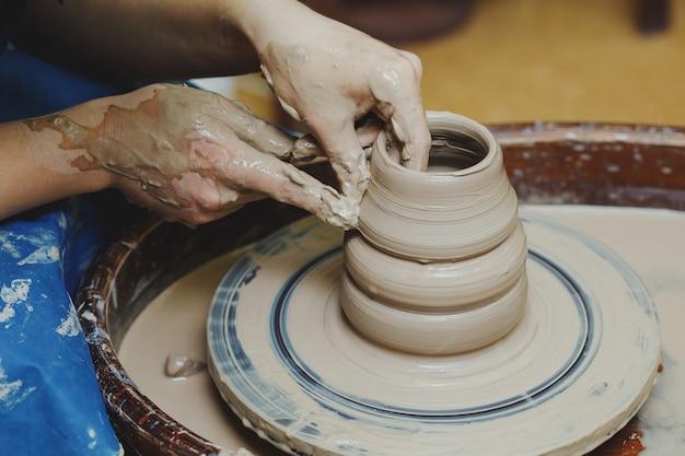 Mains de femme sur potier. artisan artiste façonne le pot