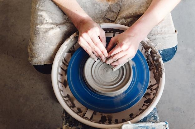 Mains de femme pratiquant la poterie en céramique
