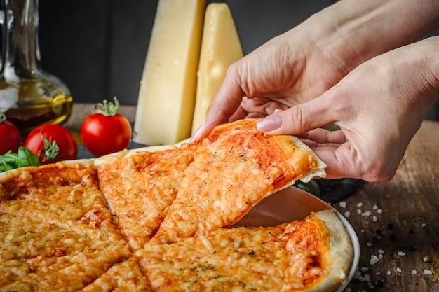 Les mains de la femme prend un morceau de pizza