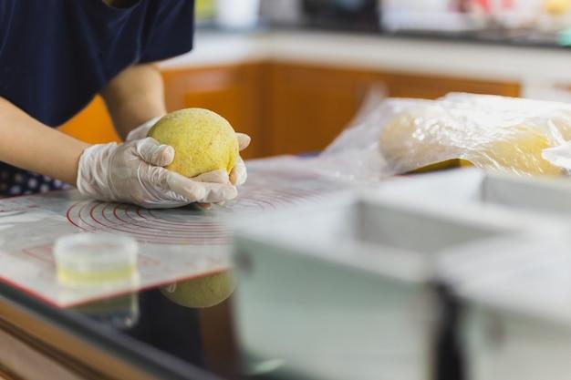 Mains de femme préparant la pâte à pain sur la table de la cuisine.