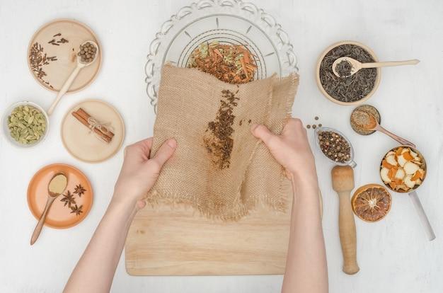Mains de femme préparant le thé masala indien avec des épices