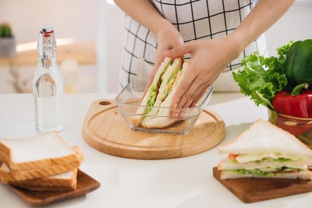 Les mains d'une femme préparent une boîte à lunch à l'école. c'est plus intéressant pour les enfants.